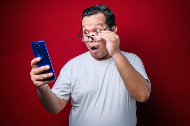 Ein asiatischer typ, der ein weißes t-shirt trägt, sieht überrascht von den guten nachrichten, die er von seinem smartphone erhalten hat. männer zeigen geschockte bewegungen mit hervortretenden augen beim herunterrollen der brille auf einem smartphone
