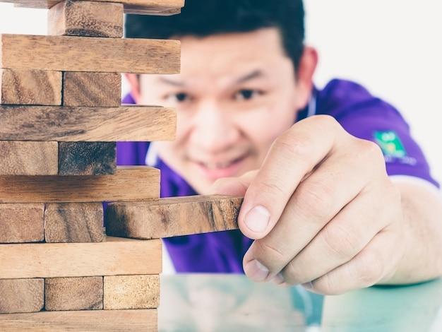 Ein asiatischer typ spielt ein turmspiel aus holzblöcken, um körperliche und geistige fähigkeiten zu üben