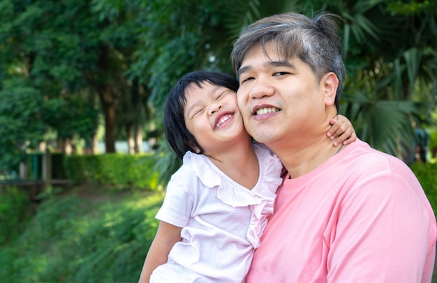 Ein asiatischer vater trägt eine schöne tochter an die brust.