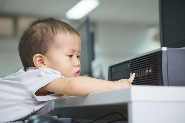 Ein asiatisches baby, das versucht, tischrechner zu benutzen