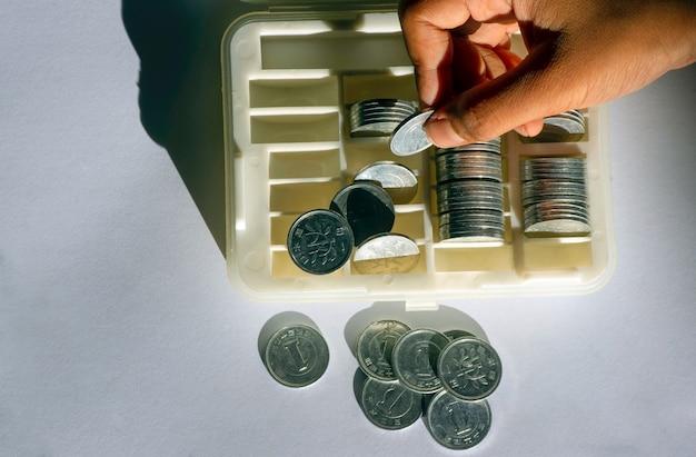 Ein asiatisches kind hält eine japanische yen-münze, 1 yen, auf der münzbox im flachen fokus. sparkonzept.