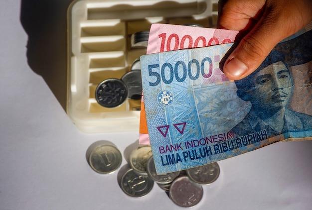 Ein asiatisches kind hält indonesisches geld mit dem hintergrund der münzbox im flachen fokus. speichern und geben konzept.