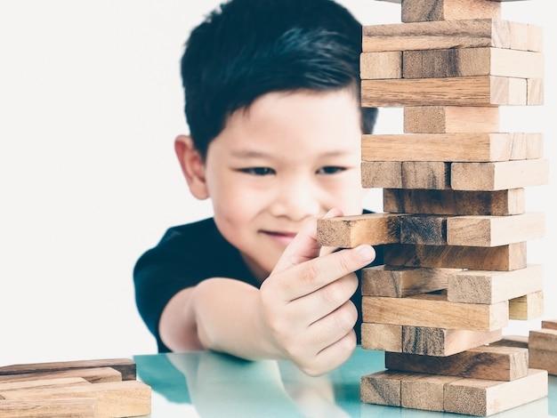 Ein asiatisches kind spielt ein turmspiel aus holzblöcken, um körperliche und geistige fähigkeiten zu üben