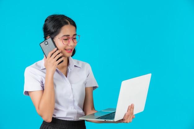 Ein asiatisches kursteilnehmermädchen, das ihr notizbuch auf einem blau anhält.
