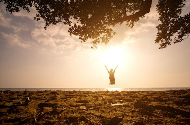 Ein asiatisches mädchen, das auf den strand zur sonnenuntergangzeit springt