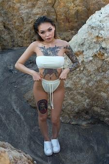 Ein asiatisches mädchen mit einem tattoo in einem weißen bikini posiert in den bergen