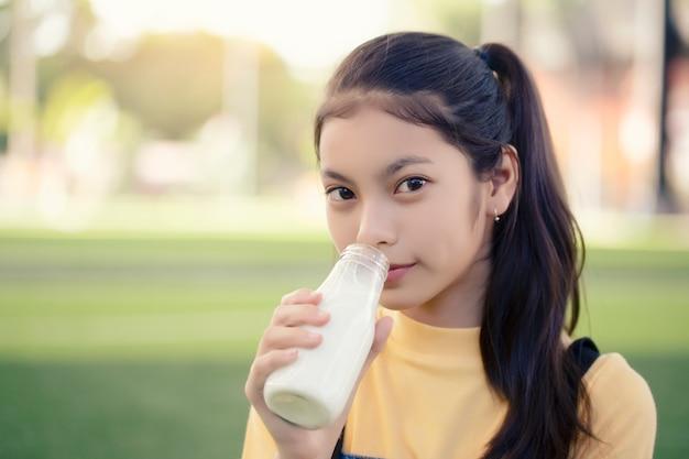 Ein asiatisches mädchen trinkt eine köstliche flasche milch.