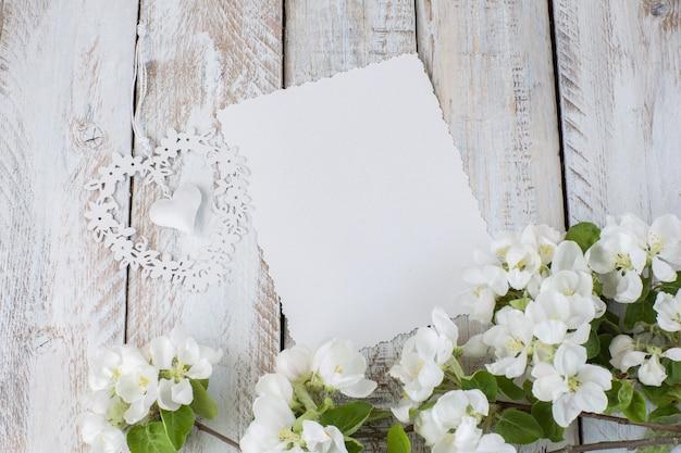 Ein ast eines blühenden apfelbaumes, ein blatt papier und ein maßwerk herz
