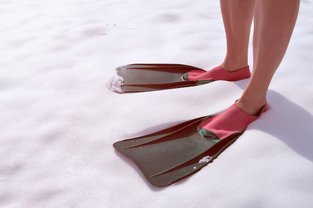 Ein athlet in schwimmflossen steht auf dem schnee