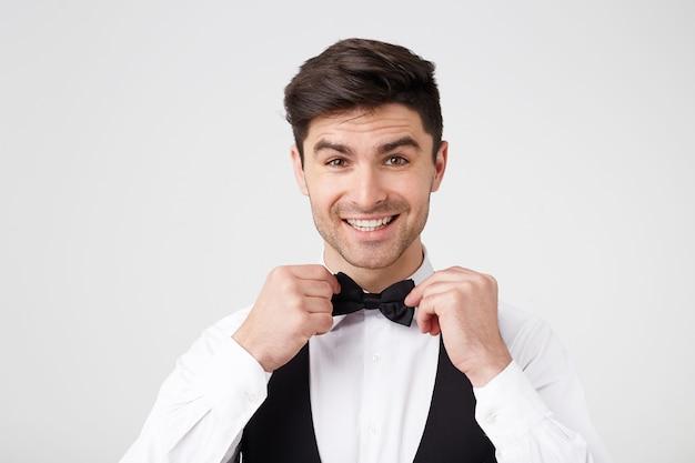 Ein attraktiver charmanter mann bereitet sich in einem schicken anzug auf den abendball vor
