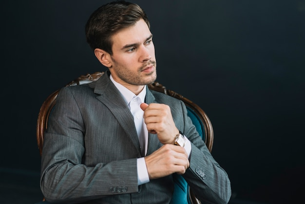 Ein attraktiver hübscher junger mann, der auf weinlesestuhl gegen schwarzen hintergrund sitzt