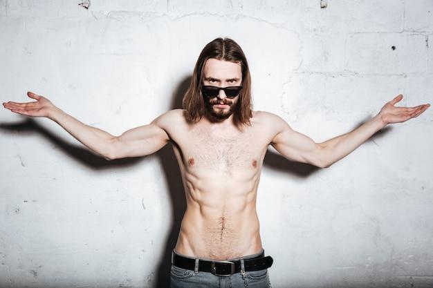 Ein attraktiver junger bärtiger hipster-mann mit sonnenbrille, der isoliert über der wand steht und mit den händen gestikuliert