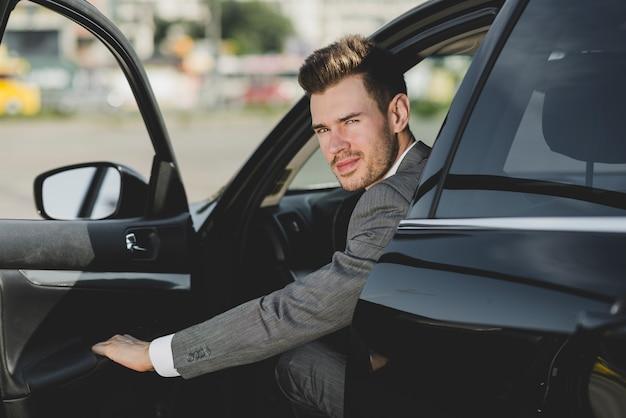 Ein attraktiver junger geschäftsmann, der heraus vom auto schaut