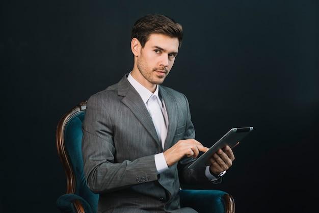 Ein attraktiver junger geschäftsmann, der im lehnsessel unter verwendung der digitalen tablette sitzt
