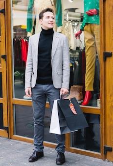 Ein attraktiver junger mann, der außerhalb des shops in der hand hält einkaufstaschen steht