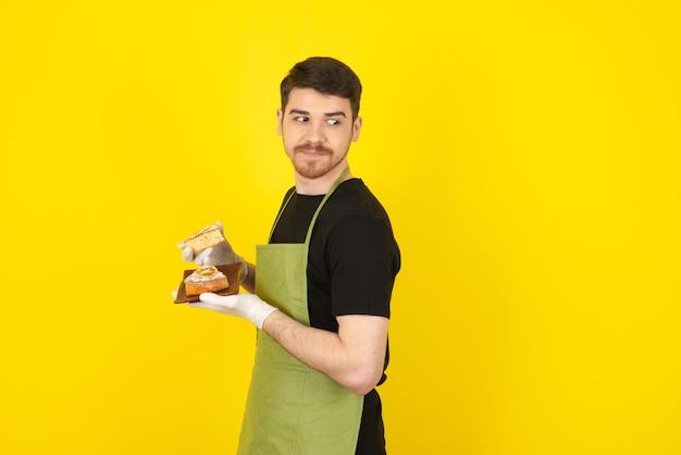 Ein attraktiver junger mann, der frische hausgemachte kuchen auf gelb hält.