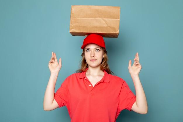 Ein attraktiver kurier der weiblichen vorderansicht in der roten kappe des roten poloshirts lächelnd, die das haltepaket über ihrem kopf auf dem blauen hintergrundlebensmittelservicejob aufwirft
