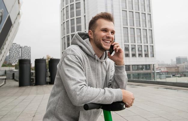 Ein attraktiver mann mit bart erzählt seinem freund am telefon von der bequemlichkeit, ein elektrofahrzeug zu mieten. umweltfreundliches transportkonzept. freizeitkleidung. wohnblöcke auf hintergrund.