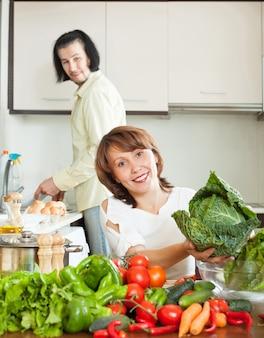 Ein attraktiver mann und eine frau mit gemüse in der küche