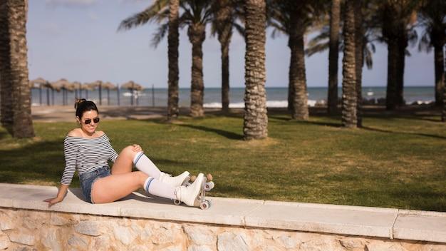 Ein attraktiver tragender rollschuh der jungen frau, der nahe dem strand sich entspannt
