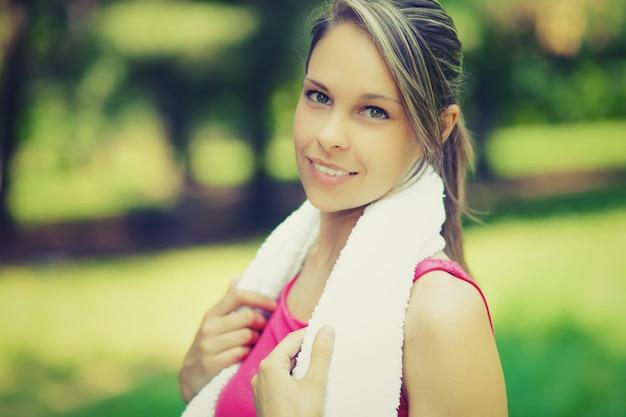 Ein attraktiver weiblicher läufer, der vor ihrem training ausdehnt
