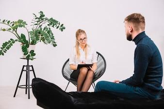 Ein attraktiver weiblicher Psychologe, der auf den männlichen Patienten sitzt auf Couch hört