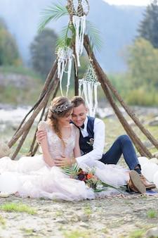 Ein attraktives brautpaar, ein glücklicher und freudiger moment. mann und frau umarmen und küssen in urlaubskleidung. hochzeitszeremonie mit boho-stil am fluss an der frischen luft.