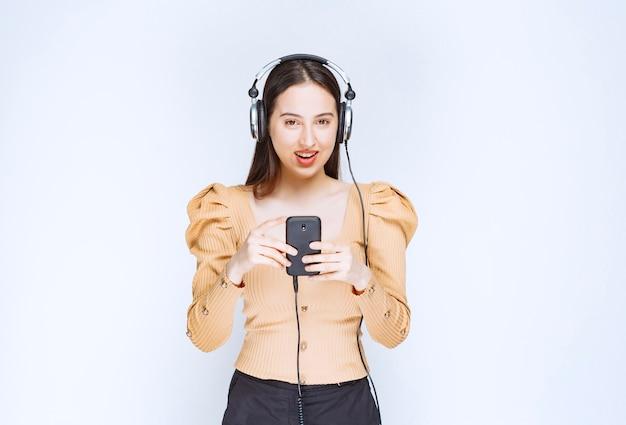 Ein attraktives frauenmodell, das musik in den kopfhörern hört.