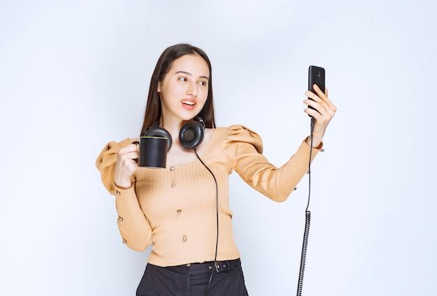 Ein attraktives frauenmodell, das selfie mit einer tasse getränk und kopfhörern nimmt.
