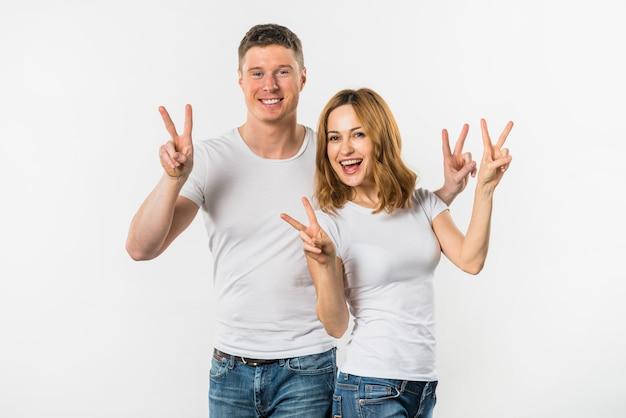Ein attraktives junges paar, das siegeszeichen gegen weißen hintergrund zeigt