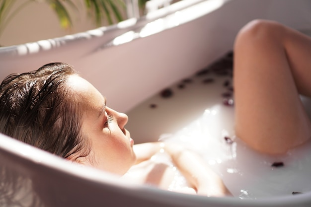 Ein attraktives mädchen, das sich im bad mit blütenblättern auf hellem hintergrund entspannt