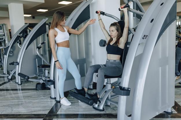 Ein attraktives mädchen im fitnessstudio schüttelt unter aufsicht eines trainers eine obere gruppe von muskeln, armen und schultern.