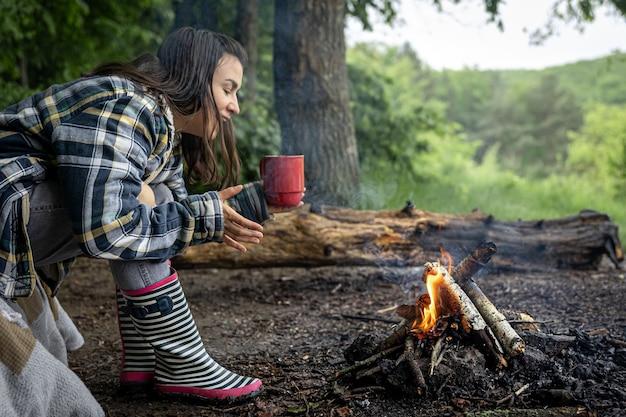 Ein attraktives mädchen mit einer tasse in der hand wärmt sich in der nähe eines feuers im wald auf.