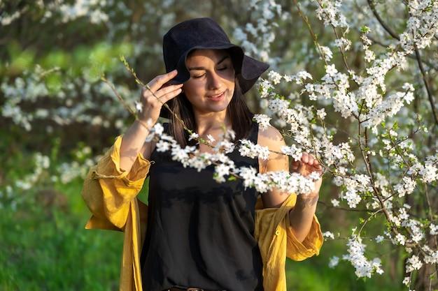 Ein attraktives mädchen mit hut zwischen blühenden bäumen genießt den duft von frühlingsblumen