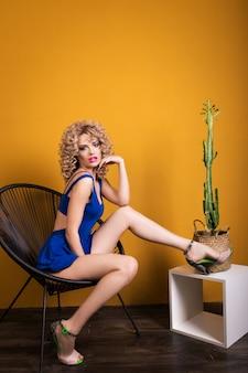 Ein attraktives mädchen sitzt auf einem stuhl mit einem kaktus. im studio auf gelb
