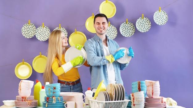 Ein attraktives paar, das gut gelaunt verliebt ist, erledigt hausarbeiten und spült nach einer party schmutziges geschirr ab