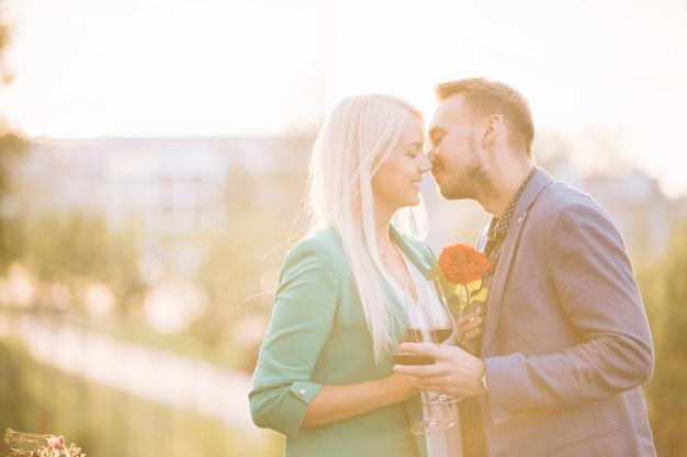 Ein attraktives paar, welches die weingläser küssen sich hält