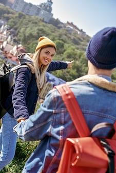 Ein attraktives reisendes mädchen zieht ihren freund mit, um mit ihr zu gehen