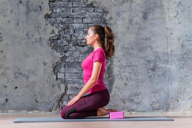 Ein attraktives übendes yoga der jungen frau gegen verwitterte wand