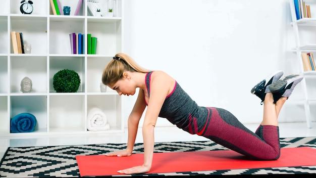 Ein attraktives übendes yoga der jungen frau zu hause