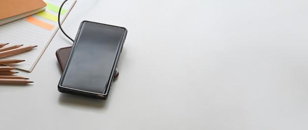 Ein aufgeladenes smartphone stellt einen weißen arbeitstisch auf, der von verschiedenen geräten umgeben ist