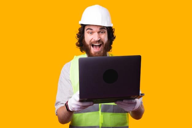 Ein aufgeregter junger architekt hält einen computer in der hand und sieht ihn in der nähe einer gelben wand sehr schockiert an