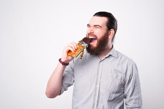 Ein aufgeregter junger bärtiger mann isst glücklich eine schokolade nahe einer weißen wand