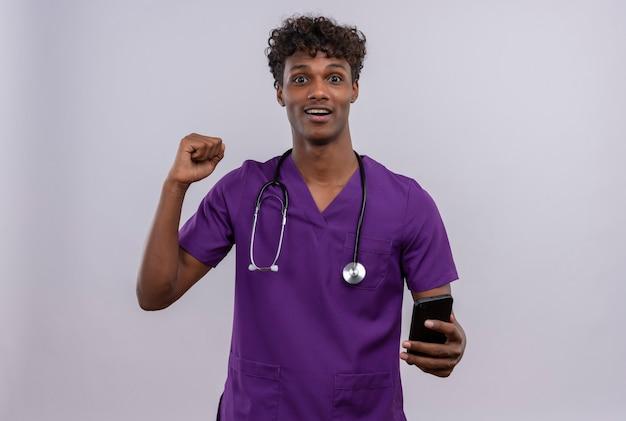 Ein aufgeregter junger gutaussehender dunkelhäutiger männlicher arzt mit lockigem haar in violetter uniform mit stethoskop, der sein smartphone mit geballter faust betrachtet