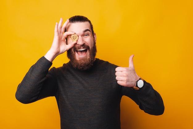 Ein aufgeregter junger mann hält ein bitcoin in die nähe seines auges und ist glücklich damit