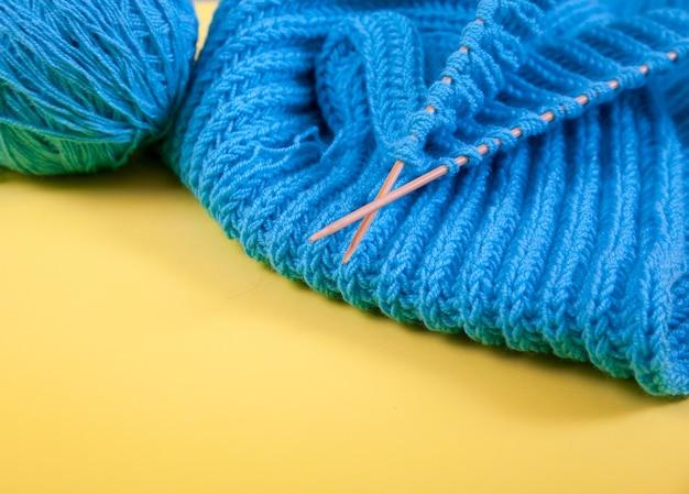 Ein aufgerollter handgestrickter blauer schal, wollknäuel und stricknadeln