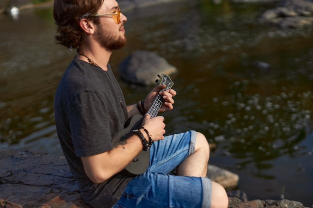 Ein aufgeweckter mann sitzt auf einem felsen am see, spielt ukulel und schaut in die ferne das konzept der ...