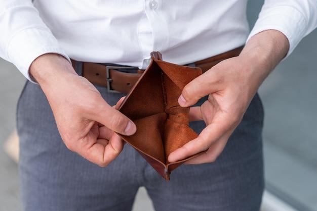 Ein aufgrund der krise entlassener mitarbeiter öffnet seine leere brieftasche.