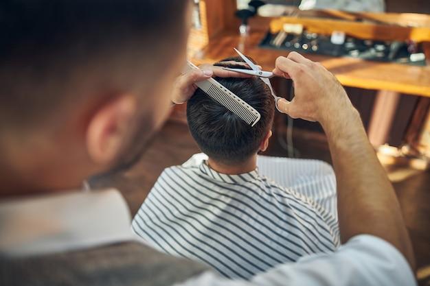 Ein aufmerksamer friseur, der seinem kunden in einem modernen friseursalon einen frischen haarschnitt verpasst