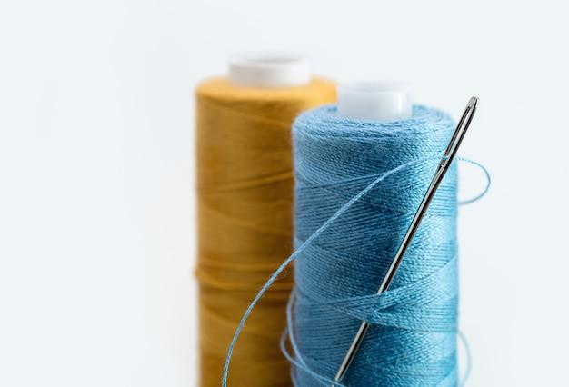 Ein aufrecht stehender strang aus blauem und gelbem faden, silberne nadel.